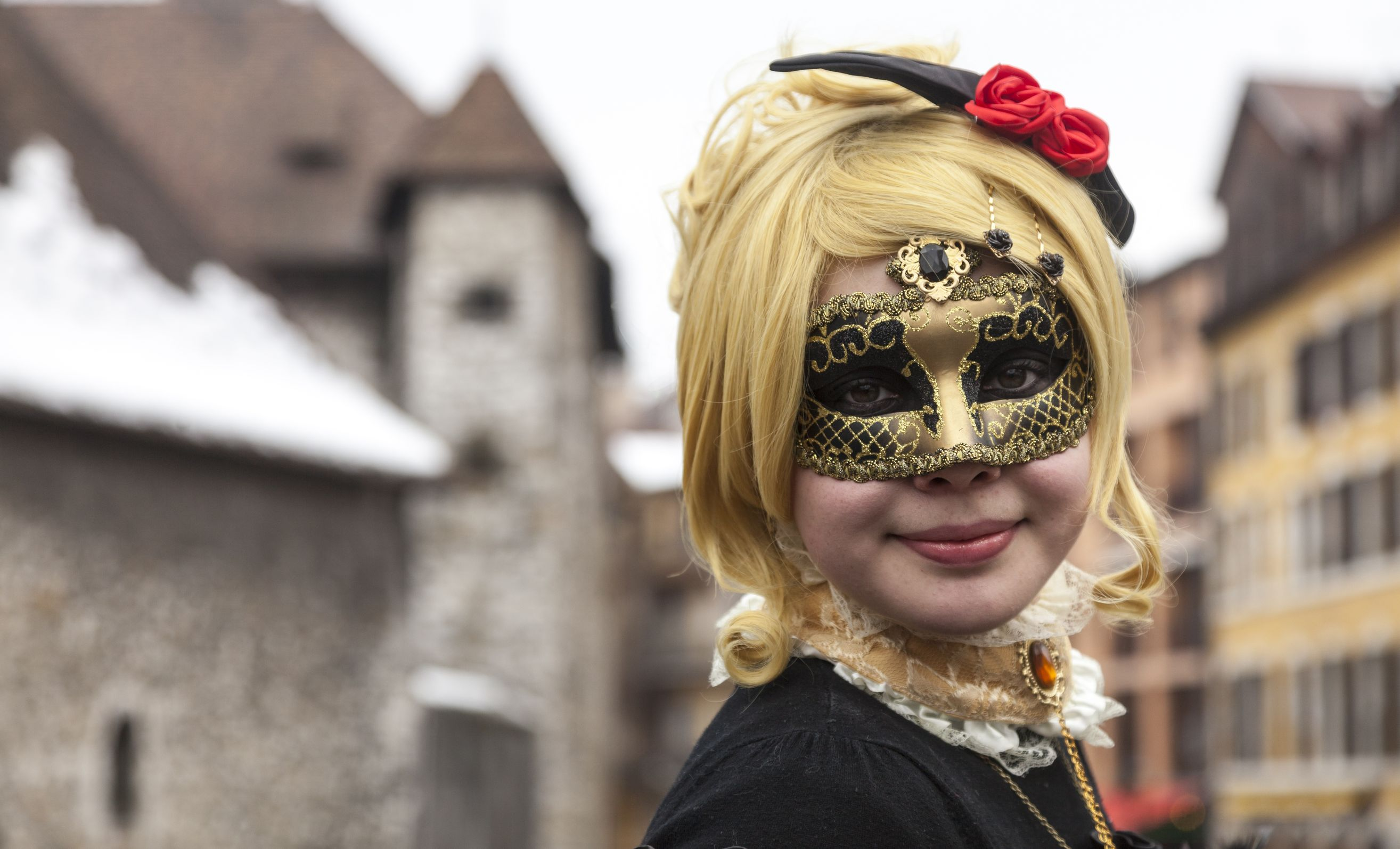 18321492 - annecy, france, february 23, 2013: environmental portrait of a girl in colombina mask posing in front of the palais de l'isle in annecy during a venetian carnival which celebrates the beauty of the real venice.